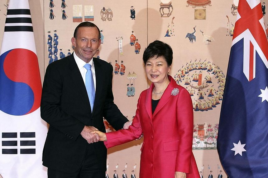 Australian Prime Minister Tony Abbott (left) shakes hands with South Korean President Park Geun Hye before their meeting at the presidential house in Seoul on Tuesday, April 8, 2014. South Korea and Australia signed a free trade deal on Tuesday