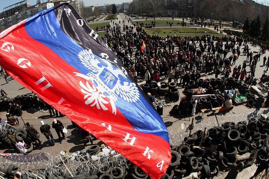 The flag of the so-called Donetsk Federative Republic waves above a barricade and a crowd gathered in front of the Donetsk regional administration building, held by pro-Russian militants, on April 8, 2014. Moscow said on Tuesday it was ready to
