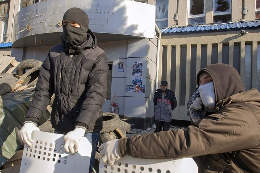 Pro-Russian protesters gather at a barricade outside the offices of the SBU state security service in Luhansk, in eastern Ukraine on Tuesday, April 8, 2014.Ukraine's acting president said Tuesday he would treat Russian separatists who have seiz