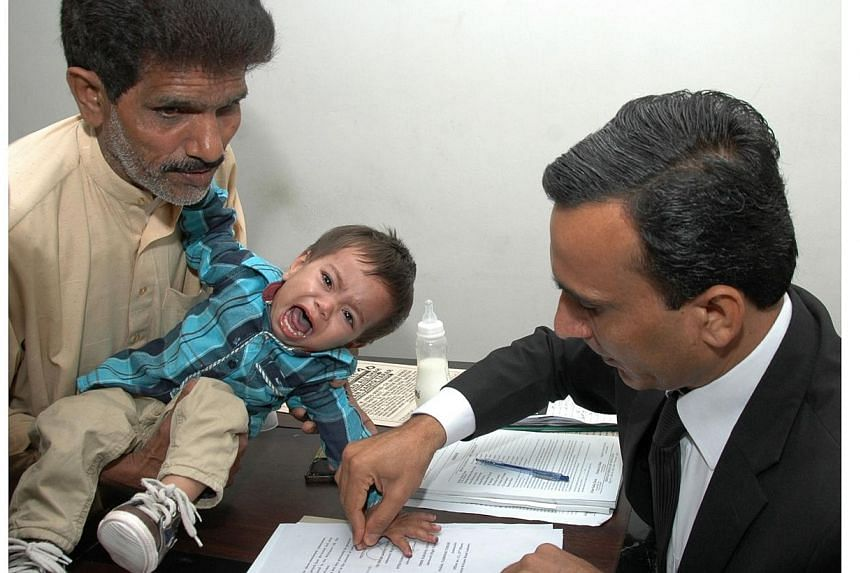 This photograph taken on Tuesday, April 3, 2014 shows a Pakistani lawyer taking the thumb impression from nine-month-old toddler Mohammad Musa on a bail bond in Lahore.Relatives of a nine-month old baby charged with attempted murder in Pakistan