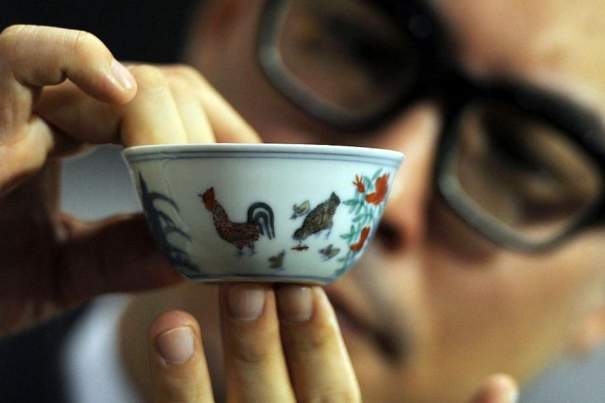 The Meiyintang Chenghua 'Chicken Cup' is displayed by deputy chairman for Sotheby's Asia Nicolas Chow after it was sold for a record price in Hong Kong on April 8, 2014. -- PHOTO: AFP