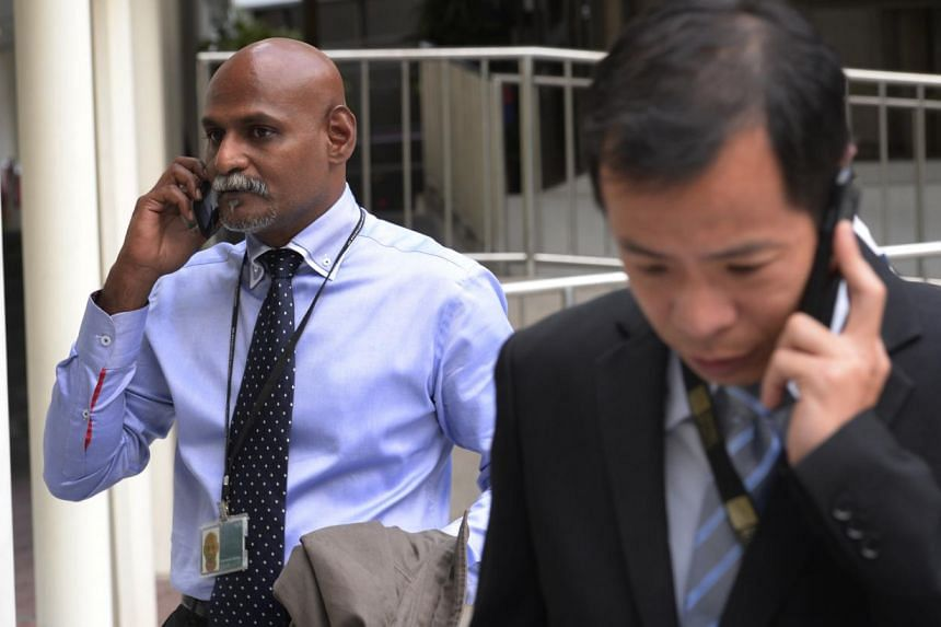 DSP Subramaniam N (left) and CID IO Inspector Chris Lee Tian Huat, leave the State Courts on 7 April, 2014. Construction worker Mahalingam Thavamani had insisted on entering an area in the vicinity of the Little India riot on Dec 8 last year, despite