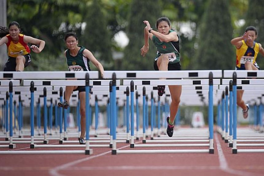 Jannah Wong (second from right) of Raffles Institution in action during the A-Girls 100 Metres Hurdles at the Schools' National Track and Field Championships on 8 April, 2014. Trailing her are (from left) Janine Foo of Hwa Chong Institution, Laura Ta