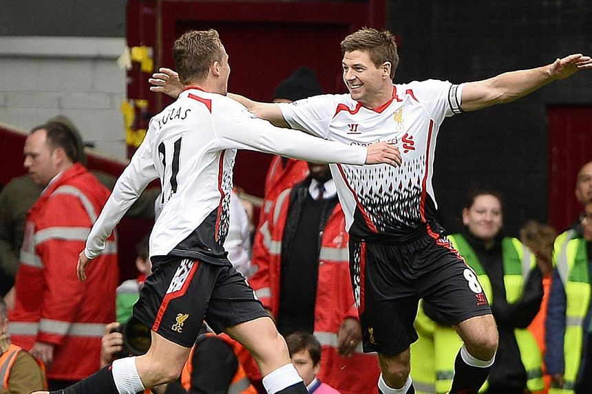 Liverpool captain Steven Gerrard (above right) put his club back at the top of the EPL with two high-pressure penalties against West Ham. The Reds escaped unscathed from a  contentious Hammers goal, in which goalkeeper Simon Mignolet (below right)  w