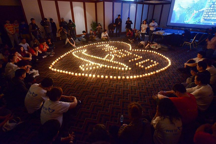 Chinese relatives of passengers on the missing Malaysia Airlines flight MH370 take part in a prayer service at the Metro Park Hotel in Beijing on April 8, 2014.-- PHOTO: AFP