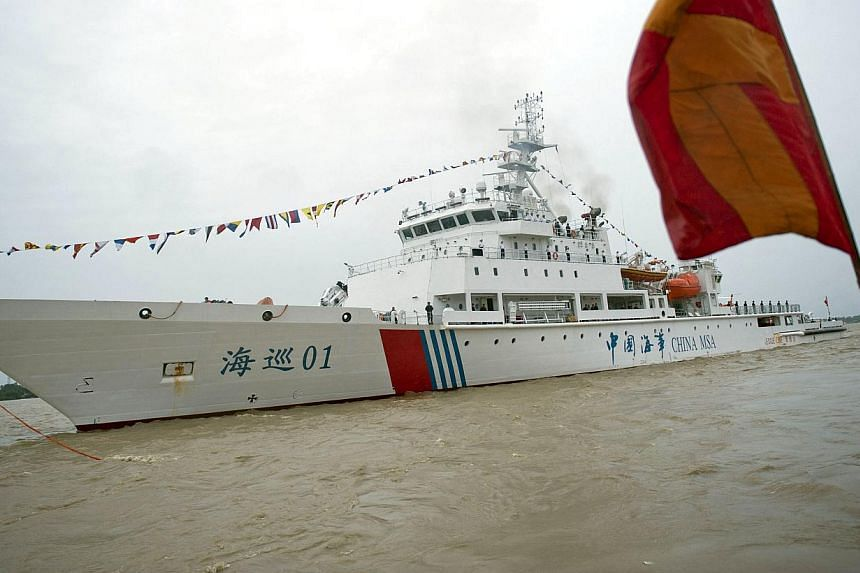 """This photograph taken on July 24, 2013 shows crew members standing on the deck of the vessel """"Haixun 01"""" of China's Maritime Safety Administration (MSA) at Bo Aung Kyaw Jetty in Yangon. The Chinese ship searching for Malaysia Airlines Flight MH370 de"""