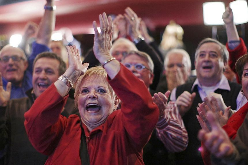 People cheering at the Quebec Liberal leader Philippe Couillard's provincial election rally headquarters in St. Felicien, Quebec on April 7, 2014. -- PHOTO: REUTERS