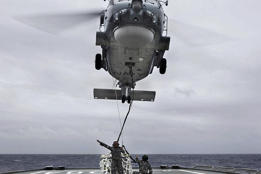 A helicopter from Australian Navy ship HMAS Toowoomba unloads supplies on the deck of HMAS Success. The HMAS Success alone costs around A$550,000 (S$640,000) a day to operate. -- PHOTO: REUTERS/AUSTRALIAN DEFENCE FORCE