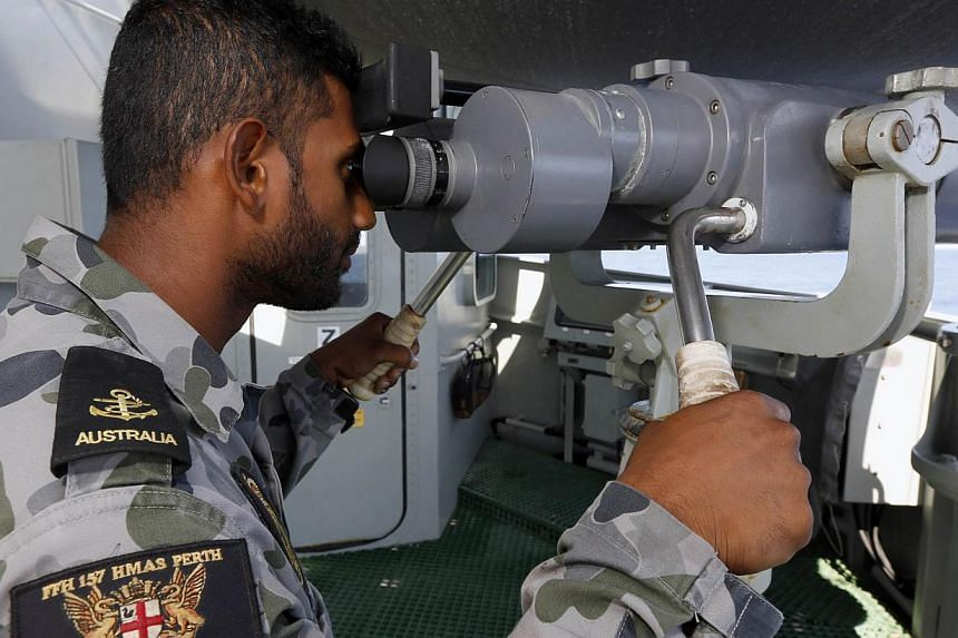 A crew member looks through the telescopic binoculars on the starboard bridge wing aboard the Australian Navy ship HMAS Perth in the southern Indian Ocean, during the search for the missing Malaysian Airlines flight MH370 on April 8, 2014. -- PHOTO: