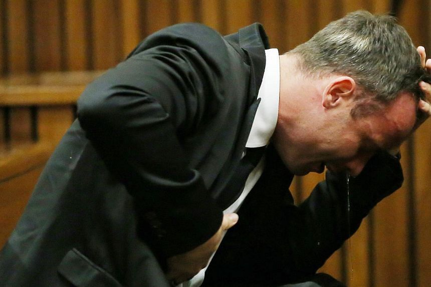 South African Paralympic track star Oscar Pistorius reacts as he listens to evidence by a pathologist during his trial in court in Pretoria on April 7, 2014. Pistorius broke down in tears in the dock on Tuesday, forcing an adjournment in his murder t
