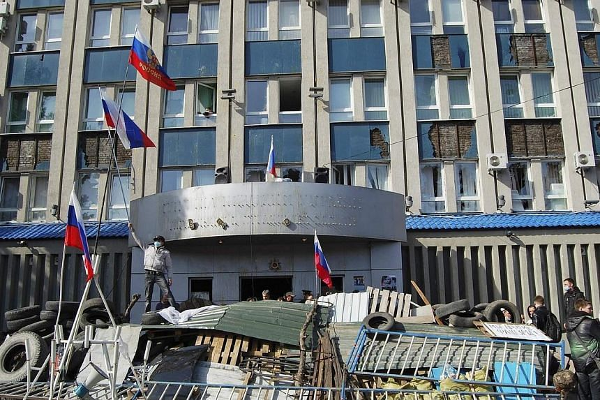 "Pro-Russian protesters gather at a barricade outside the offices of the SBU state security service in Luhansk, in eastern Ukraine April 7, 2014. NATO's chief warned Russia on Tuesday, April 8, 2014, it would be committing a ""historic mistake"" if"