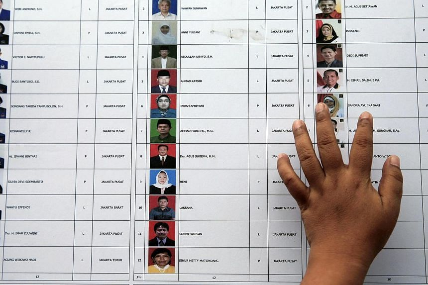 A woman places a hand on a list of candidates for members of parliament at a polling station during voting for parliamentary elections in Jakarta April 9, 2014.Indonesians are directly voting for their representatives in 19,699 legislative seat
