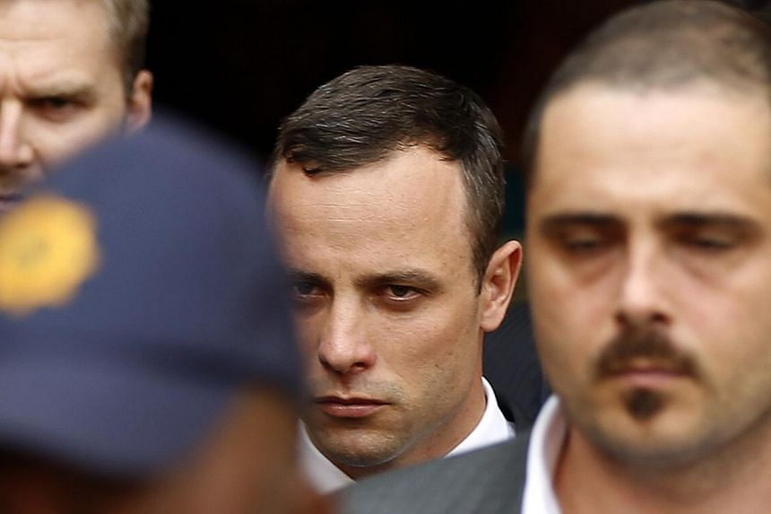 South African Olympic and Paralympic track star Oscar Pistorius (Center) leaves after his trial at the high court in Pretoria April 8, 2014.Oscar Pistorius insisted on Wednesday he never intended to kill his girlfriend, as the prosecution began