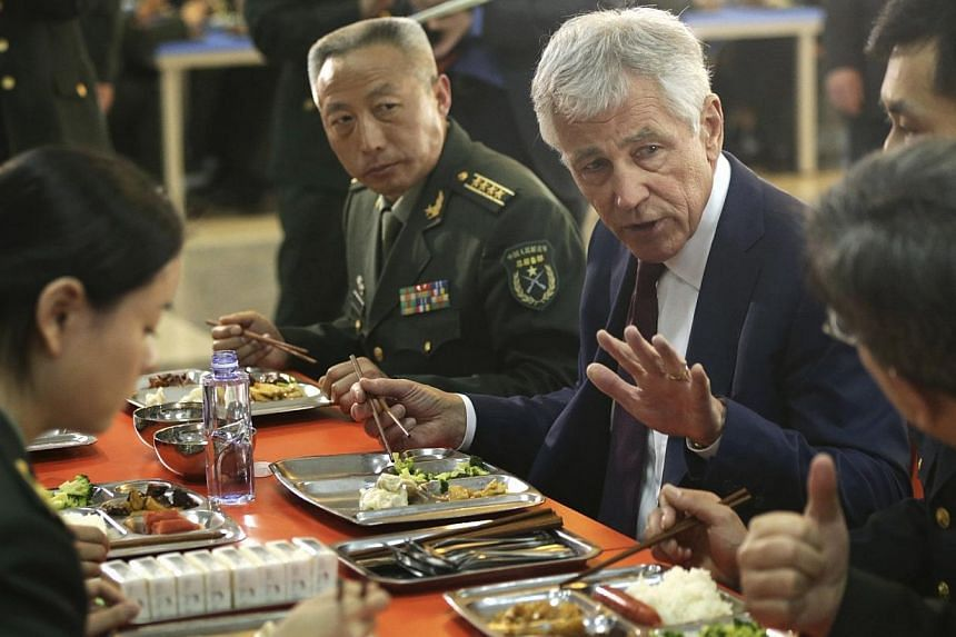 U.S. Secretary of Defense Chuck Hagel eats with students at the mess hall of the Non-Commissioned Officer Academy during a tour in Changping District of Beijing on April 9, 2014. Over kung pao chicken and dumplings, Pentagon chief Chuck Hagel re