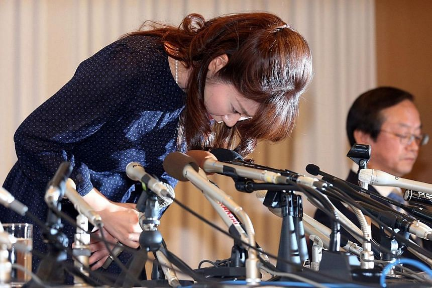 Haruko Obokata (left), 30, a female researcher of Japan's Riken Institute bows as she apologises at a press conference in Osaka, western Japan on April 9, 2014, following claims that her ground-breaking stem cell study was fabricated.A young fe