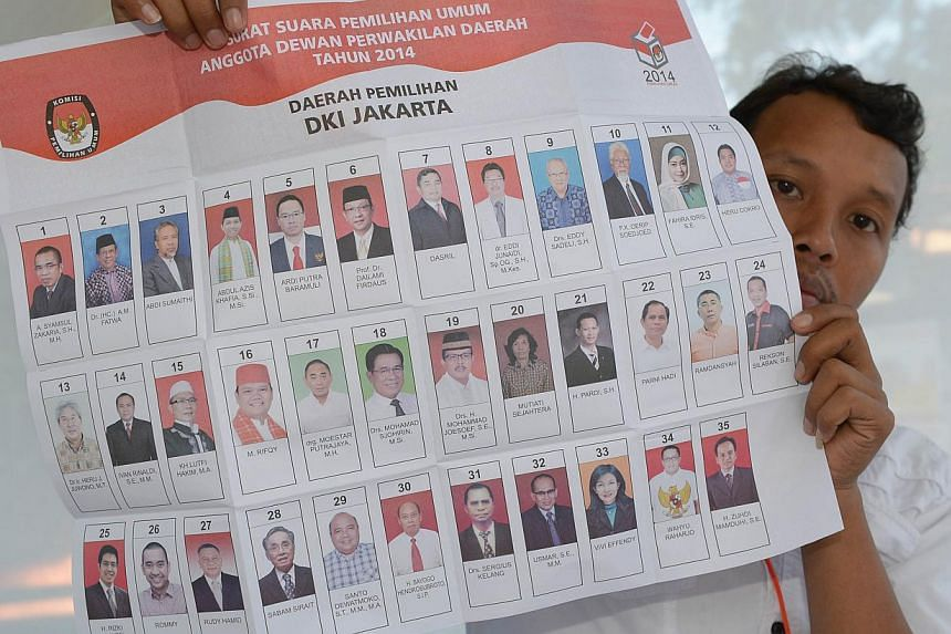 A Poll official holds a ballot paper during legislative polls in Jakarta on April 9, 2014. -- PHOTO: AFP