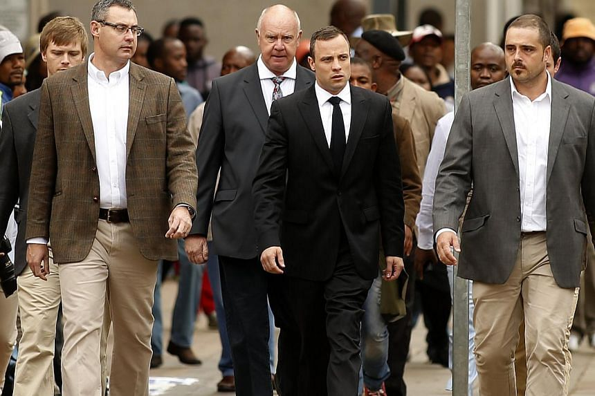 Olympic and Paralympic track star Oscar Pistorius (centre) arrives ahead of his trial at the North Gauteng High Court in Pretoria on April 9, 2014. Oscar Pistorius on Wednesday denied any intention to kill girlfriend Reeva Steenkamp, or the intr