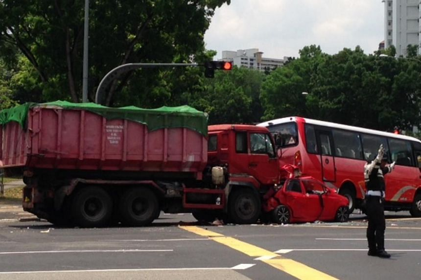 A motorcyclist died after his machine was sandwiched between a tipper truck and a minibus at the junction of Ang Mo Kio avenues 6 and 1. -- ST PHOTO: JOYCE FANG
