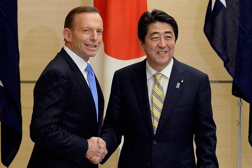 Australian Prime Minister Tony Abbott (left) shakes hands with his Japanese counterpart Shinzo Abe prior to a National Security Council meeting at the latter's official residence in Tokyo on April 7, 2014. -- FILE PHOTO: AFP