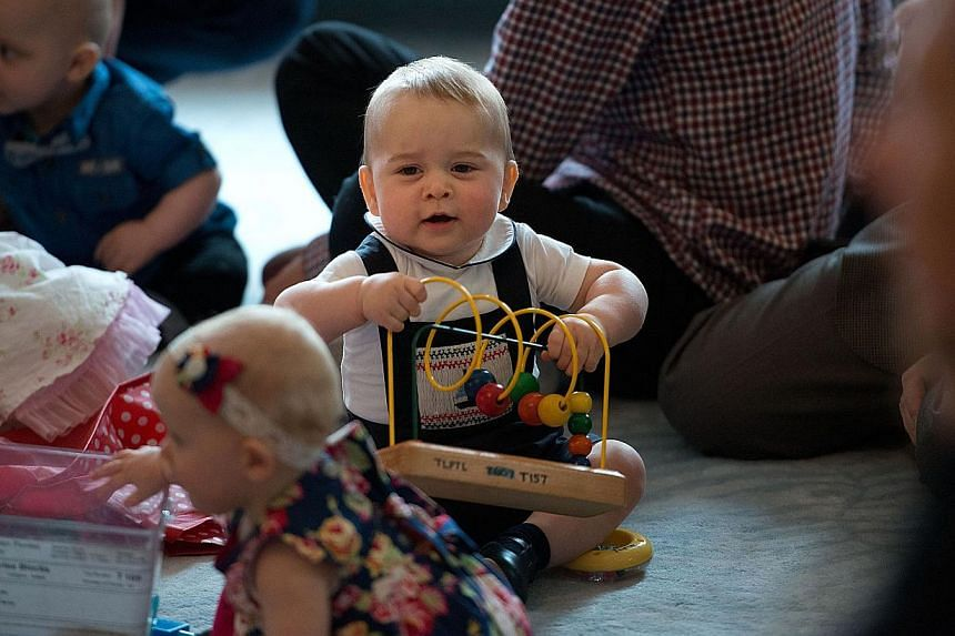 Britain's Prince George (centre) plays with toys during a visit to the Plunket nurse and parents group at Government House in Wellington on April 9, 2014. -- PHOTO: AFP
