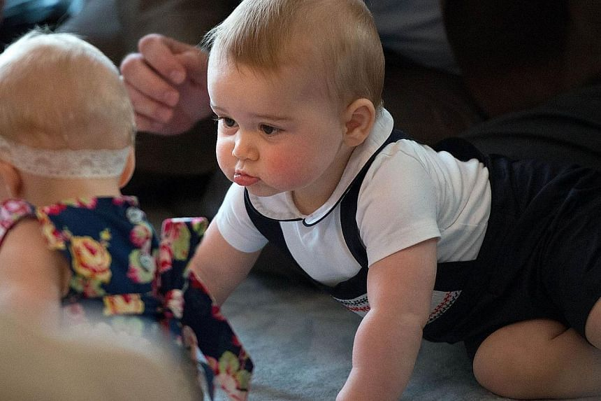 Britain's Prince George (right) plays in front of baby Eden Alve (left) during a Plunket nurse and parents group visit at Government House in Wellington on April 9, 2014.-- PHOTO: AFP