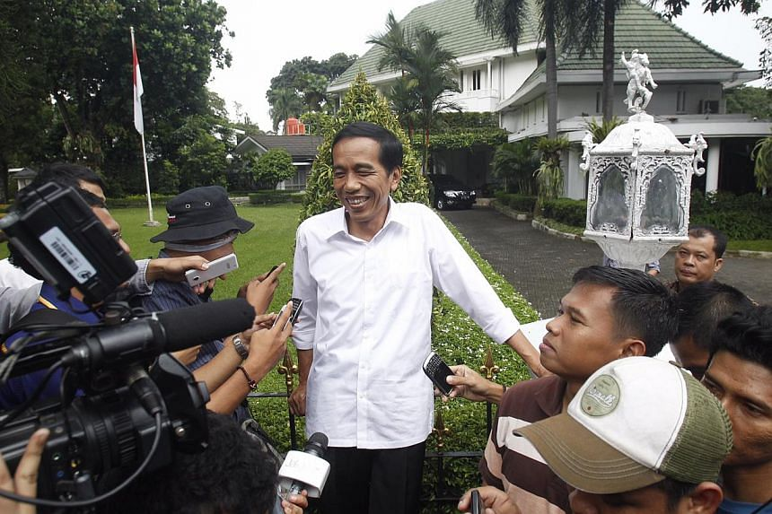 Jakarta Governor and PDI-P presidential candidate Joko Widodo is all smiles when asked about the lead maintained by his party in a quick count of polls. He was swarmed by reporters waiting outside his house in Jakarta on April 9, 2014. -- PHOTO