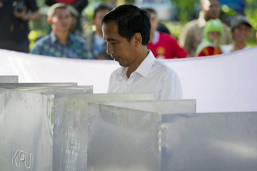 Jakarta Governor Joko Widodo and presidential candidate of the opposition Indonesian Democratic Party of Struggle (PDI-P) voting at a polling centre during the legislative election in Jakarta on April 9, 2014. -- PHOTO: AFP