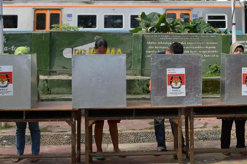 Indonesian voters choose their candidates as a train passes by at a polling station during legislative elections in Jakarta on April 9, 2014. -- PHOTO: AFP