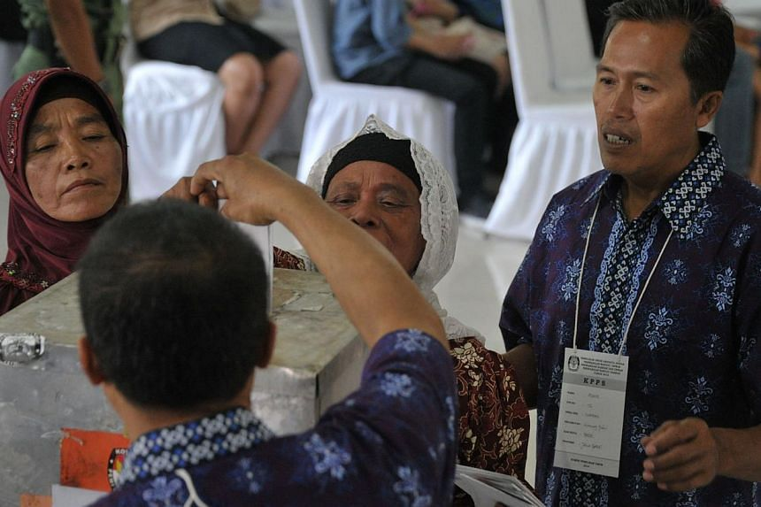 Indonesians cast at polling station during the legislative election in Jakarta on April 9, 2014. -- PHOTO: AFP