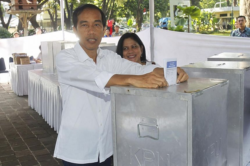 Jakarta governor and PDI-P presidential candidate Joko Widodo, 52, and his wife Iriana, 50, casting their votes on polling day in Jakarta, Indonesia on 9 April 2014. -- ST PHOTO: KEVIN LIM