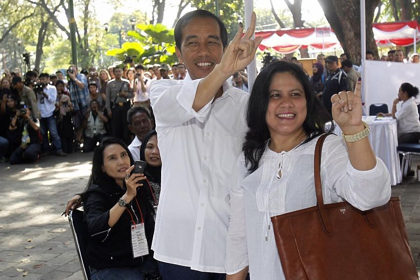Jakarta governor and PDI-P presidential candidate Joko Widodo, 52, and his wife Iriana, 50, after casting their votes on polling day in Jakarta, Indonesia on 9 April 2014. -- ST PHOTO: KEVIN LIM