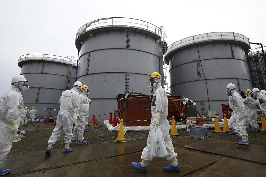 Members of the media and Tokyo Electric Power Co. (TEPCO) employees wearing protective suits and masks walk past storage tanks for radioactive water in the H4 area at the tsunami-crippled TEPCO Fukushima Daiichi nuclear power plant in Fukushima prefe