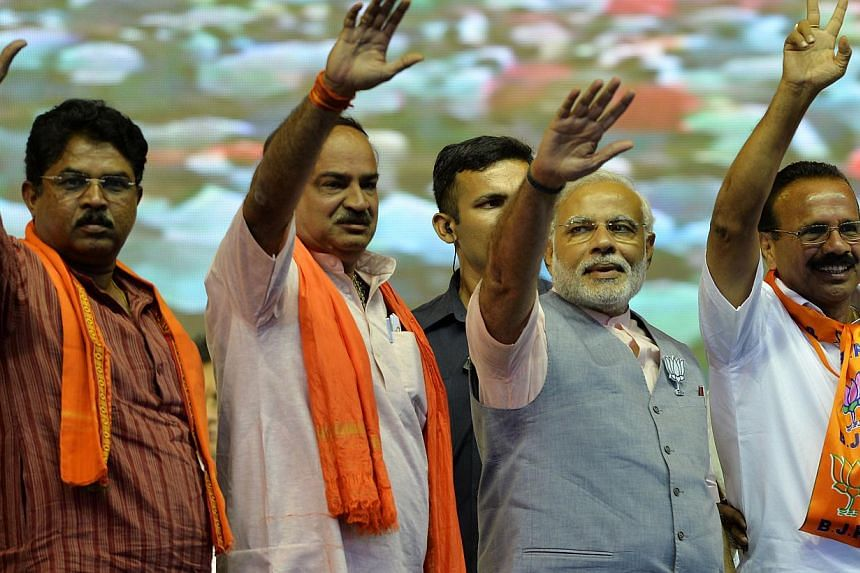 "Chief Minister of the western Indian state of Gujarat and Bharatiya Janata Party (BJP) Prime Ministerial andidate Narendra Modi (2nd right) waves to supporters alongside state BJP leaders during the ""Bharat Vijay"" rally held on the outskirts of Banga"