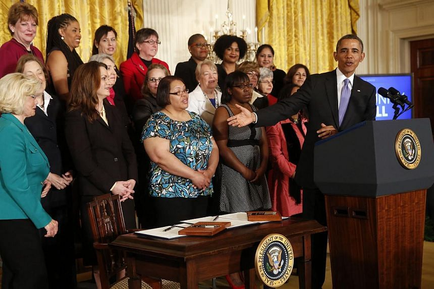 United States President Barack Obama gestures toward Lilly Ledbetter (left) before signing two new executive actions aimed at increasing transparency about women's pay during an event at the White House in Washington on April 8, 2014. -- PHOTO: REUTE