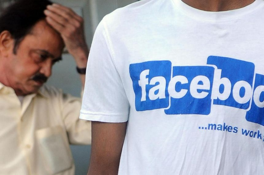 In this photograph taken on May 14, 2012, an Indian officegoer walks past a youth wearing a t-shirt with a Facebook logo at a market in Mumbai.Facebook has hit more than 100 million users in India, making it only the second country after the Un