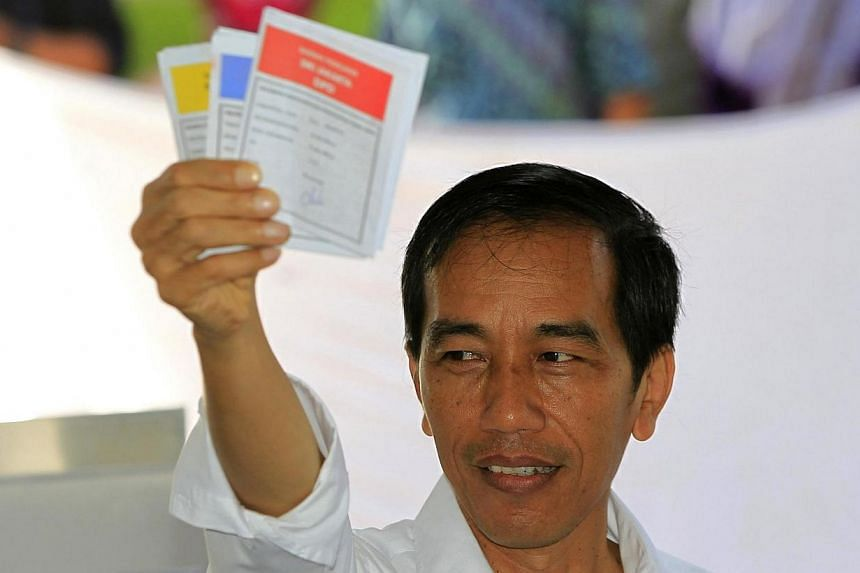 Jakarta Governor and presidential candidate from the Indonesian Democratic Party-Struggle (PDI-P) party, Joko Widodo, shows his ballot paper during voting in the parliamentary elections in Jakarta on April 9, 2014. His hands-on approach and his image