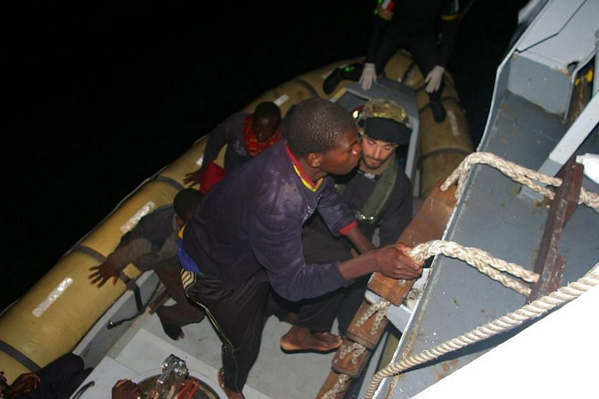 This picture released on April 8, 2014 by The Marina Militare shows rescuers of the Italian Navy helping refugees to climb on their boat near the Italian port of Pozzallo, south of Sicily. Italy has rescued 4,000 migrants from boats trying to re