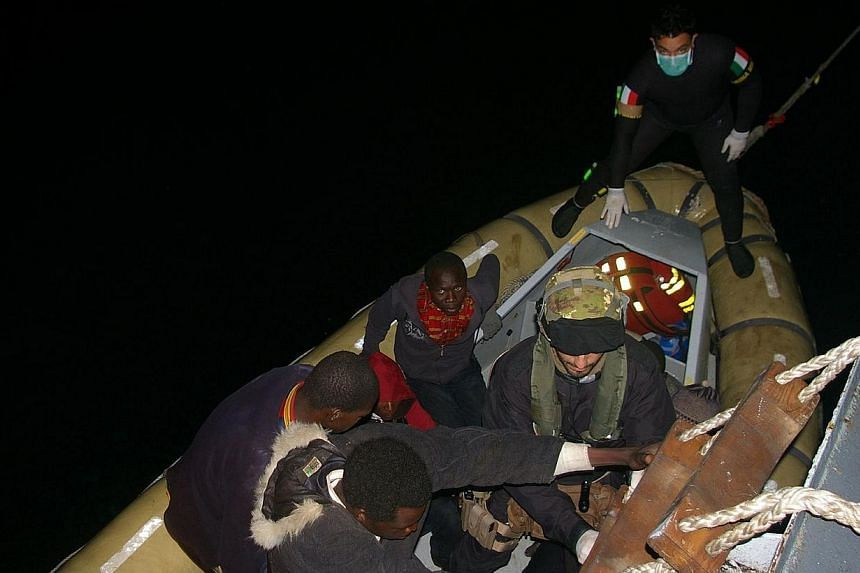 This handout picture released on April 8, 2014 by The Marina Militare shows rescuers of the Italian Navy helping refugees to climb on their boat near the Italian port of Pozzallo, south of Sicily.Italy has rescued about 4,000 immigrants trying