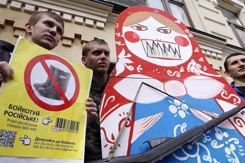 """Protesters hold """"an angry Matryoshka"""" with a weapon and placard reading """"Boycott Russia !"""" during an action in central Kiev, on April 9, 2014, calling for the boycott of Russian goods.Four-way talks between the United States and the European Un"""