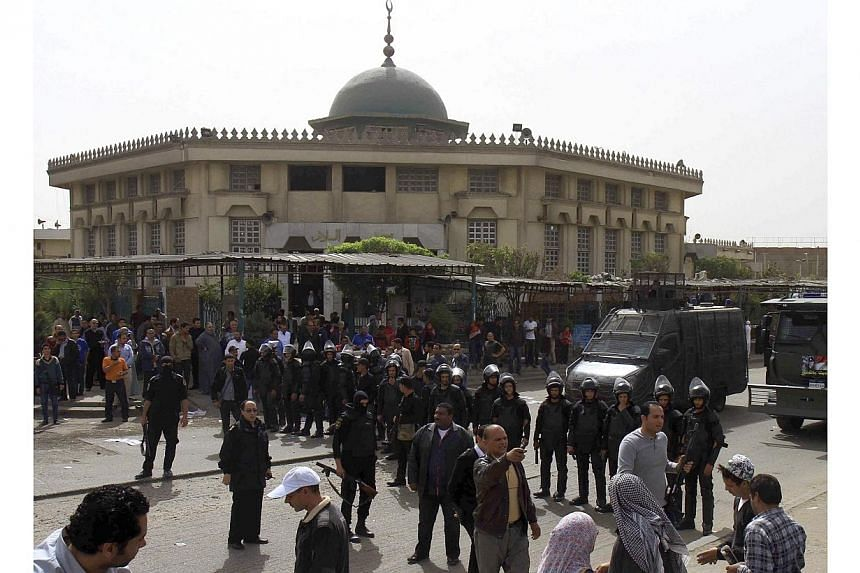 Policemen stand guard in front of a mosque during Friday prayer ahead of a protest by supporters of Islamist President Mohamed Mursi, who was overthrown by the army after demonstrations against his rule last July, in Cairo, March 7, 2014.The Eg
