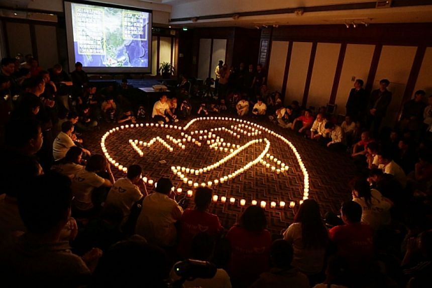 Family members pray around 239 lit candles during a candlelight vigil for passengers onboard the missing Malaysia Airlines Flight MH370 in the early morning, at Lido Hotel, in Beijing April 8, 2014, after a month of searching for the missing aircraft