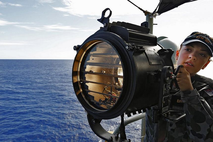 This handout photo taken on April 7, 2014 and released on April 9, 2014 by Australian Defence shows Communications and Information Systems, Seaman Georgina Brooks signaling HMAS Success for a replishement at sea (RAS) on the starboard bridge wing of