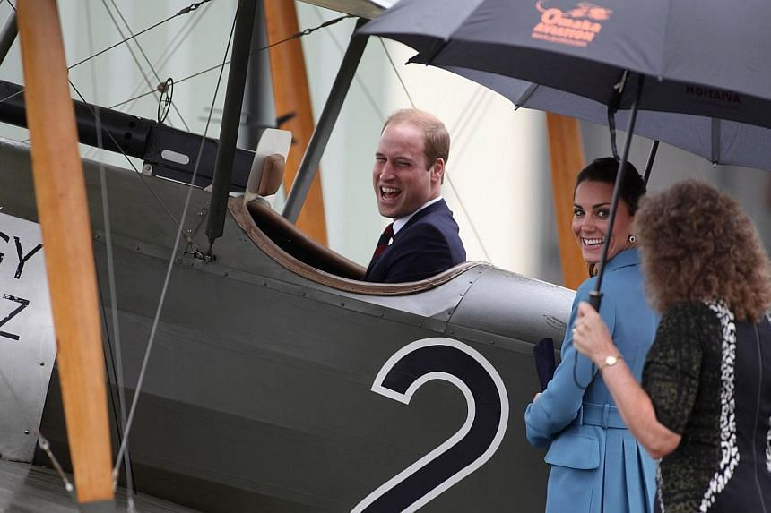 Britain's Prince William sits in the cockpit of an old Sopworth Pup single seater biplane as his wife Catherine, the Duchess of Cambridge, looks on during a visit to the Omaka Aviation Heritage Centre in the New Zealand city of Blenheim on April 10,