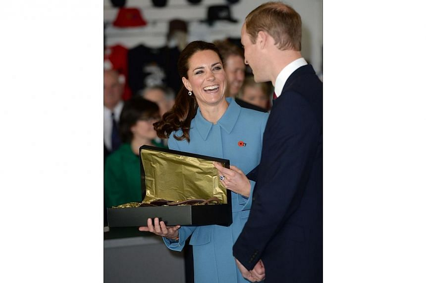 Britain's Catherine, Duchess of Cambridge and her husband Prince William react after receiving a baby size flying hat at the Omaka Aviation Heritage Centre near Blenheim, in New Zealand April 10, 2014. -- PHOTO: REUTERS