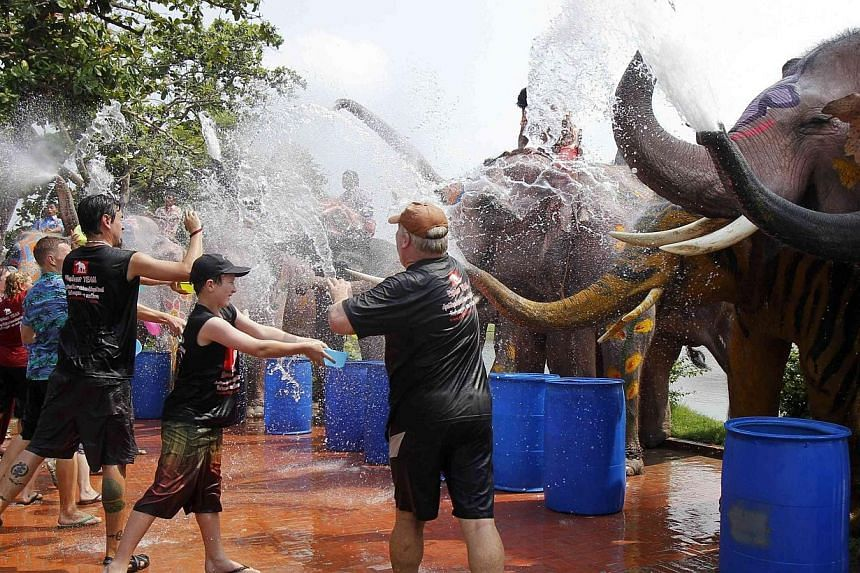 Elephants spray tourists with water in celebration of the Songkran water festival in Thailand's Ayutthaya province on April 9, 2014. -- PHOTO: REUTERS