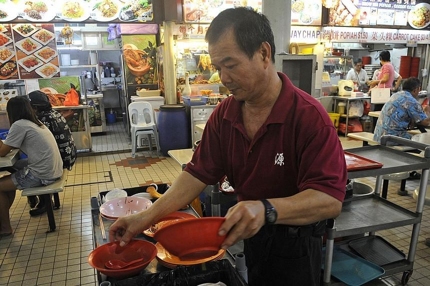 A cleaner clearing glasses and dishes at Berseh Food Centre in Jalan Besar. The National Wages Council, which is coming up with wage guidelines for the year ahead, is looking for feedback from members of the public. --  ST FILE PHOTO:
