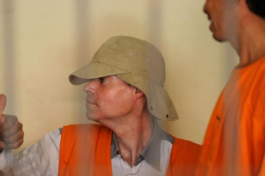Francois Giuily (center) of France, 48, waits with another prisoner in a holding cell in Denpasar court on Indonesia's resort island of Bali on April 10, 2014. A Frenchman appeared in court in Bali on Thursday, 10 April, 2014, accused of traffic