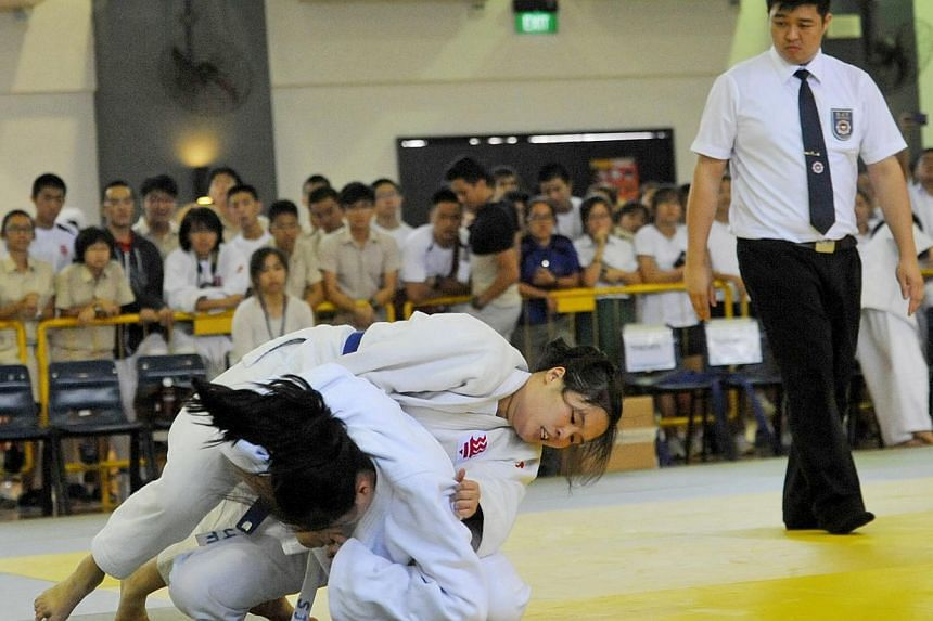 Ashley Tan Si Yin from Hwa Chong Institution (on top, blue belt) in a match up against Joyce Lee from Raffles Institution competing for the Schools' National A Division judo heavyweight championship on April 2.-- ST FILE PHOTO: MATTHIAS HO