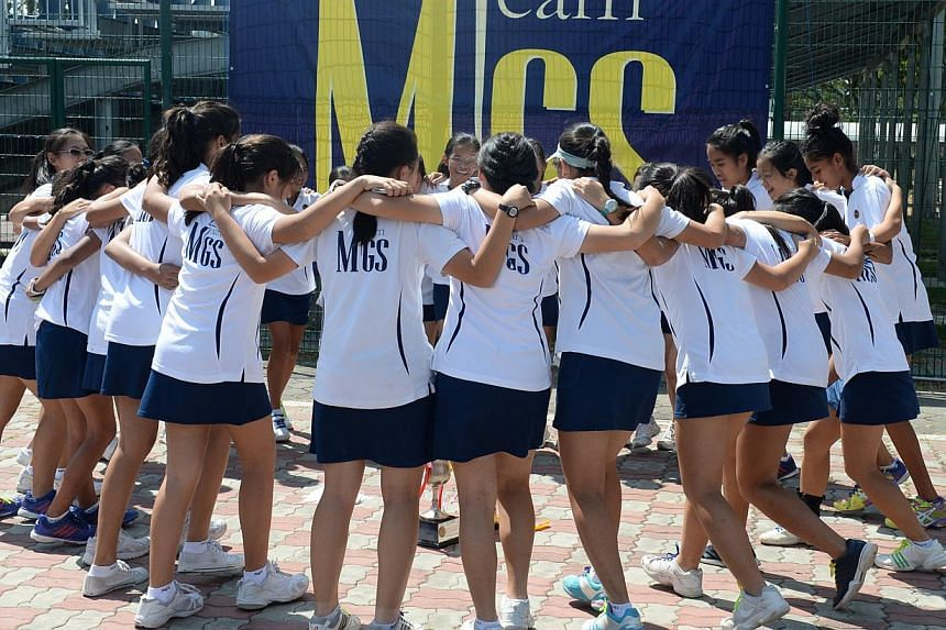 Methodist Girls' School celebrating their fourth straight B Division tennis title over Raffles Girls' School (RGS) at the Kallang Tennis Centre on March 5.-- ST FILE PHOTO: AZIZ HUSSIN