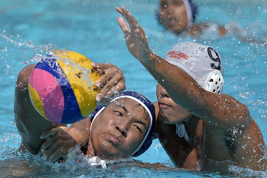 Daryl Ho of Anglo-Chinese Junior College (left) being marked closely by Hwa Chong Institution's Lim Wen Bin during the Schools' National A Division water polo finals on April 3.-- ST FILE PHOTO: MUGILAN RAJASEGERAN